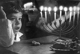 Un enfant devant une hanoukkia brillant de tous ses feux à Zot Hanoucca (8e jour).