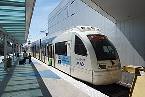 A MAX train stopped with its doors open and passengers boarding it at Portland International Airport station