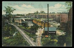 A 1911 postcard showing a quarrying operation in Portland Connecticut with cliffs of brownstone in the background, rail lines for loading and transporting stone, industrial buildings, rail carts, and other parts of the operation.