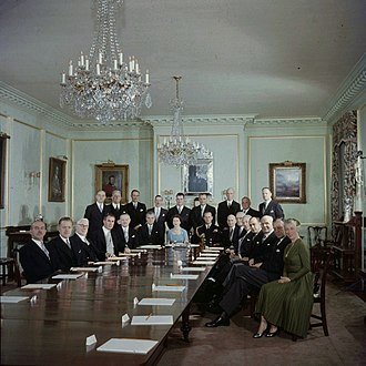Queen's Privy Council for Canada - The first meeting of the Privy Council before the reigning sovereign; in the State Dining Room of Rideau Hall, Queen Elizabeth II is seated at centre, with Prince Philip, Duke of Edinburgh, to her left, and Prime Minister John Diefenbaker at her right; 14 October 1957