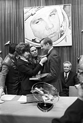 A black-and-white image. Armstrong has his left side facing us, he is holding a book and wearing civilian formal dress. A woman with bouffant hair is pinning a badge to his lapel. Two men in Soviet uniform and one in civilian garb are watching, on the wall in the background is a large photo of a cosmonaut. In the foreground on a table is a model of two spacecraft docking.