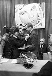 Een zwart-witafbeelding.  Armstrong heeft zijn linkerkant naar ons gericht.  Hij houdt een boek en draagt burgerlijke formele kleding.  Een vrouw met bouffant haar pakt een insigne op zijn revers.  Twee mannen in sovjetuniform en één in burgerkleding kijken toe.  Op de muur op de achtergrond staat een grote foto van een kosmonaut.  Op de voorgrond op een tafel staat een model van twee ruimtevaartuigen die aanleggen.