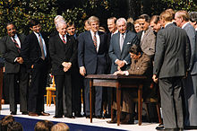 Rangel and about fourteen other men standing around a table, where President Ronald Reagan signs a bill