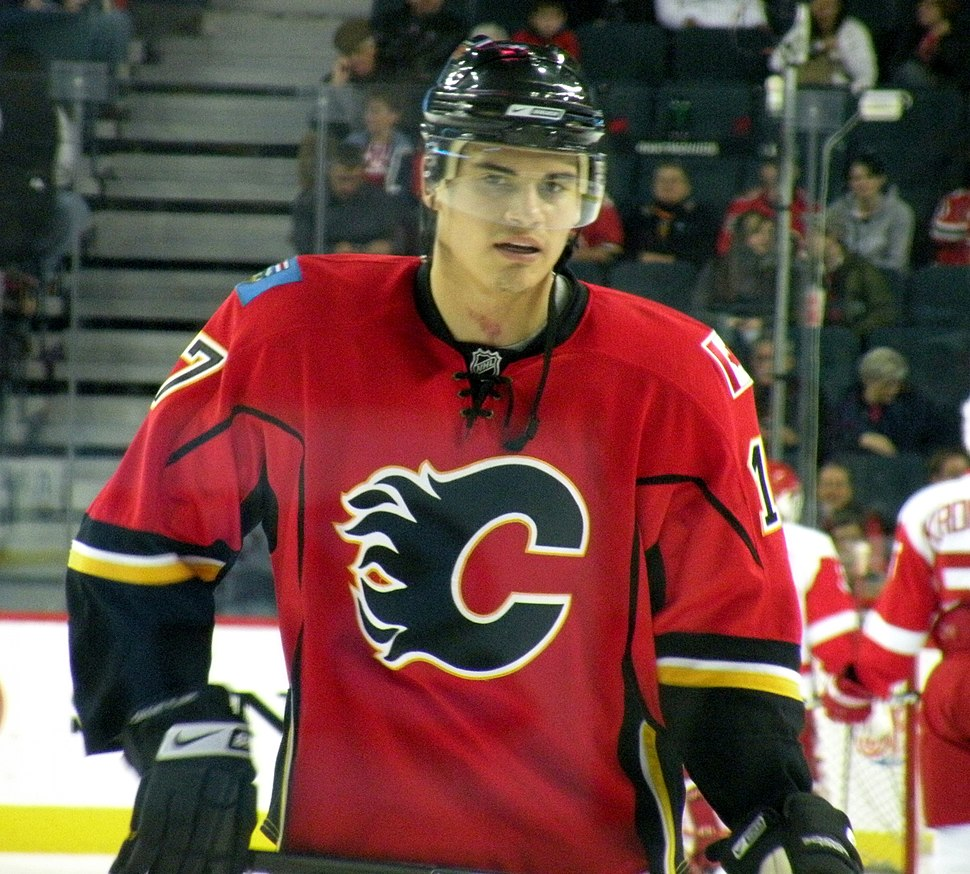 A player stares into the distance. He is wearing a red uniform with black and yellow trim and a stylized black C on his chest.
