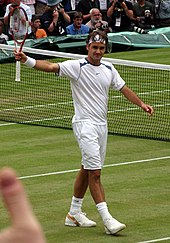 A dark-haired man is waving to the crowd with his tennis racket in his right hand, and he is wearing all white clothing