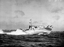 Ship speeding at sea with a white bow wave; land can be seen in the background