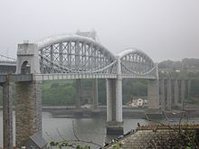 a bridge spanning a river at high level, the bridge deck supported in the centre by curved tubular metal girders