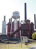 "Photograph of the Sloss Blast Furnaces, dominated by the smokestacks and a water tower marked ""Sloss"". In the foreground is an informational sign discussing the Furnaces' National Historic Landmark status."