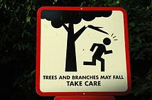A sign with a figure running under a branch