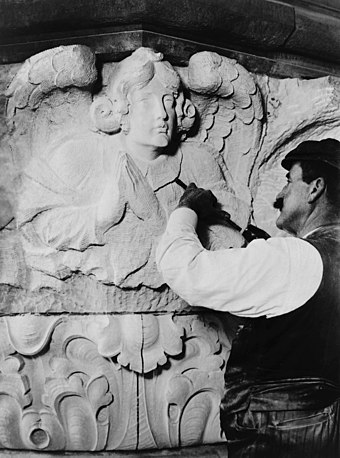 Stone carver carving stone, at the Cathedral of Saint John the Divine, New York, 1909.