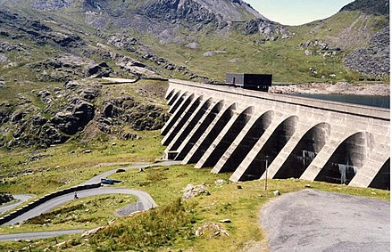 The Llyn Stwlan dam of the Ffestiniog Pumped Storage Scheme in Wales. The lower power station has four water turbines which can generate a total of 360 MW of electricity for several hours, an example of artificial energy storage and conversion. Stwlan.dam.jpg
