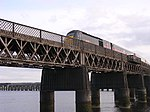 Train on the Tay Rail bridge. This view of the rail bridge is taken from the extreme west edge of the grid box. The stumps of the first rail bridge which collapsed in a storm in 1879 are just visible at the foot of the current pillars mid river and beyond, the hills of Fife.