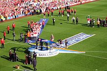 A coloured photograph of a trophy presentation which took place on the Highbury pitch