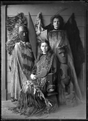 Two unidentified European women in a display of Maori cloaks, weapons, implements, and wooden carved figures. ATLIB 272347.png