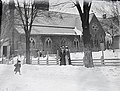 Two women watching a child in the snow outside a church building. (17218493786).jpg