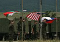 U.S. Marine Cpl. Michael J. Harding, right, a rifleman with Black Sea Rotational Force 11, raises the U.S. flag alongside Serbian and Bulgarian flags to officially begin a cooperative training evolution at 110614-M-OB762-001.jpg