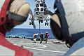 U.S. Sailors assigned to the amphibious dock landing ship USS Pearl Harbor (LSD 52) clear the ship's flight deck after connecting a cargo pendant to an AS332 Super Puma helicopter assigned to the dry cargo 130808-N-WD500-217.jpg