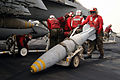 US Navy 030327-N-6817C-083 Aviation Ordnancemen move and attach precision guided ordnance to an F-A-18E Super Hornet on the flight deck aboard USS Abraham Lincoln (CVN 72).jpg