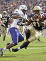 US Navy 031004-N-9693M-521 Navy slotback Tony Lane bobbles the ball and is hit by Air Force halfback Jason Boman following a caught 10-yard touchdown pass.jpg