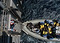 US Navy 040414-N-9630B-023 Crewmembers aboard USS George Washington (CVN 73) receive a Rigid Hull Inflatable Boat (RHIB) sent from the guided missile cruiser USS Vella Gulf (CG 72) during a passenger transfer.jpg