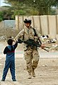 US Navy 050308-N-5319A-007 A U.S. Army Soldier assigned to 155BCT, Charlie Company, National Guard Unit from Tupelo, Miss., shakes the hand of a local Iraqi child.jpg