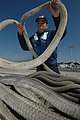 US Navy 070223-N-2060V-050 Aviation Boatswain's Mate Airman Apprentice Jose Neri on board USS Kitty Hawk (CV 63) coils and stows mooring lines after casting off fast attack submarine USS Key West (SSN 722).jpg