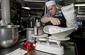 US Navy 111220-N-OY799-007 Culinary Specialist Seaman Matthew Ryback measures flour in preparation for the Christmas meal in the bake shop aboard t.jpg