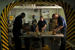 US Navy 120123-N-ZI635-172 Sailors assigned to Engineering Department construct a desk in the carpentry shop aboard the Nimitz-class aircraft carri.jpg