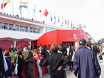 A line outside the entrance to the 2010 Venice International Film Festival with flags of several countries waving above the door