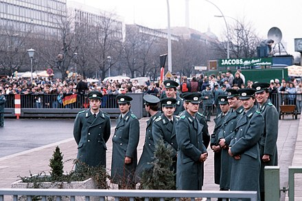 Police officers of the East German Volkspolizei wait for the official opening of the Brandenburg Gate on 22 December 1989. Volkspolizei at the official opening of the Brandenburg Gate.jpg