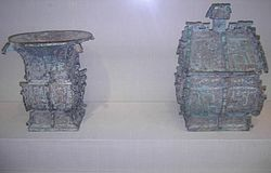 Left: Bronze 方樽 fāngzūn ritual wine container dated about 1000 BCE. The written inscription cast in bronze on the vessel commemorates a gift of cowrie shells (then used as currency in China) from someone of presumably elite status in 周 Zhōu Dynasty society. Right: Bronze 方彝 fāngyí ritual container dated about 1000 BCE. A written inscription of some 180 Chinese characters appears twice on the vessel. The written inscription comments on state rituals that accompanied court ceremony, recorded by an official scribe.