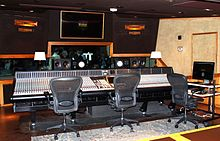 A black room containing video screens, a large mixing desk and three swivel chairs.