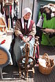 Woman spinning behind the spinning wheel at a stall with wool, etc. during the april 1 celebrations in Brielle.JPG