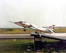 Jet aircraft, with cream and red paint scheme and an American flag on the tail, executing a ski-jump take-off, where an aircraft uses an angled ramp to increase lift before taking off