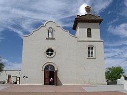 Facade of mission church showing white stucco exterior with attached bell tower to the right and attached portico to the left.