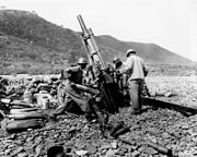 U.S. Soldiers fire a 105 mm howitzer in an indirect fire mission on the Korean battle line, near Uirson in August 1950.