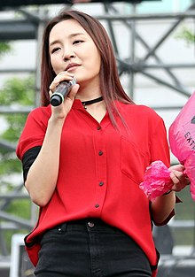 Younha leans to the left and sings into a microphone