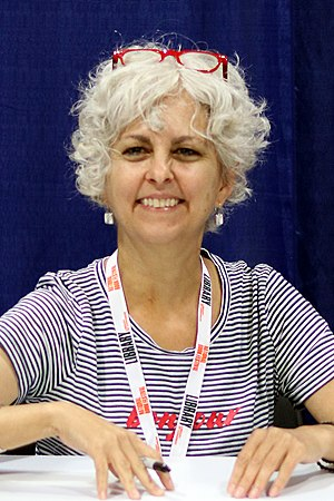 Kate DiCamillo at the 2018 U.S. National Book Festival smiling at the camera holding a pen with red glasses resting on top of her head.