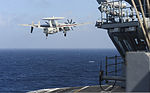 A U.S. Navy E-2C Hawkeye aircraft assigned to Airborne Early Warning Squadron (VAW) 115 flies past the aircraft carrier USS Nimitz (CVN 68) in the South China Sea Nov. 22, 2013 131122-N-TW634-246.jpg