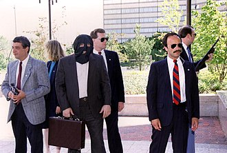 Witness protection - Staged photograph of a protected witness guarded by armed U.S. Marshals.