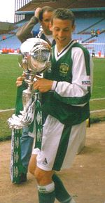 A brown-haired footballer holding a silver trophy adorned with green ribbons. He is wearing a green jersey with white sleeves, and white shorts.