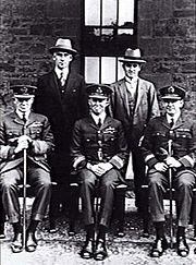 Formal portrait of five men, three seated and wearing military uniforms with peaked caps, two standing and wearing civilian clothes and hats