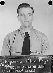 "Shepard, in Navy uniform short and tie, stands before a blackboard on which is stencilled ""Student aviator USN – 8-19-1946 class. Above that is written in chalk: ""Lt (jg) Shepard, Alan B. Jr"""