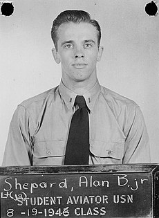 """Shepard, in Navy uniform short and tie, stands before a blackboard on which is stencilled """"Student aviator USN – 8-19-1946 class. Above that is written in chalk: """"Lt (jg) Shepard, Alan B. Jr"""""""