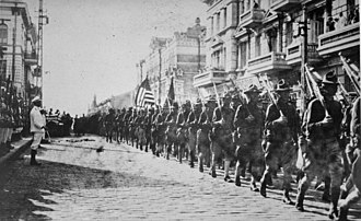 Eastern Front of the Russian Civil War - American Soldiers marching in Vladivostok in 1918, Japanese Soldiers stand at attention on the left.