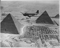 An Air Transport Command plane flies over the pyramids in Egypt. Loaded with urgent war supplies and materials, this... - NARA - 531163.tif