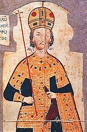 Haut du torse d'un jeune homme barbu.  Il porte une couronne dorée en forme de dôme et est vêtu d'une longue robe noire fortement brodée d'or.  Une main tient un sceptre ;  l'autre, un akakia.