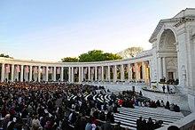 Un auditorio al aire libre con invitados sentados alineados con columnas neoclásicas y un arco cerrado en un lado y banderas de los Estados Unidos colgando entre las columnas.