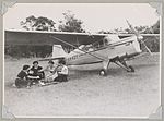 Australian Women Pilots' Association member Meg Cornwell (second from left) and three other women having a picnic on a field next to Auster J-5G Cirrus Autocar monoplane VH-ADY, 1954 (15667333374).jpg