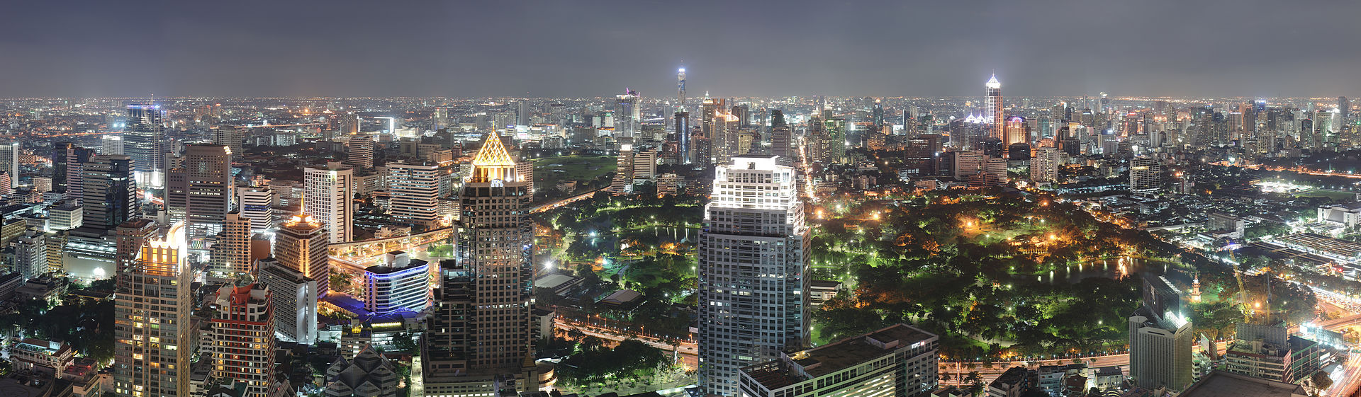Night-time panorama photograph showing an expansive cityscape with several skyscrapers in the foreground, a park in the centre, and a large group of buildings across the park